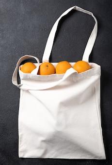디자인을 위한 흰색 쇼핑백 캔버스 천 에코 쇼핑 자루 모형, 복사 공간이 있는 검정색 질감 배경에 격리된 템플릿. 오렌지.