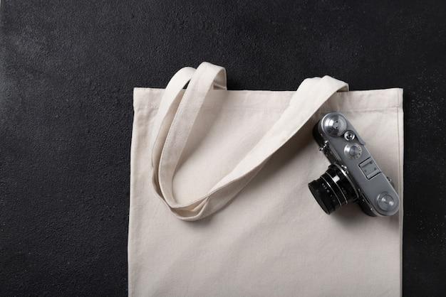 あなたのデザインのための白い買い物客バッグキャンバス生地布エコショッピングサックモックアップ、コピースペースで黒のテクスチャ背景に分離されたテンプレート。レトロなビンテージカメラ。フラットレイ。
