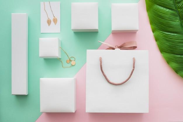 Белая сумка для покупок и подарочные коробки с драгоценными камнями на цветном фоне