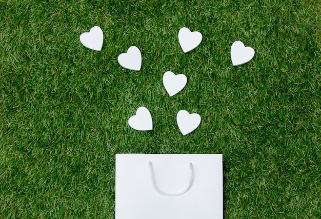White shopping bag and heart shapes on green grass.