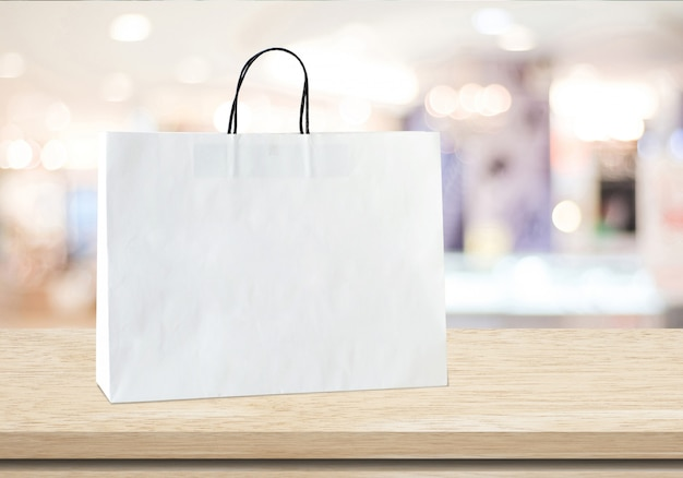 White shopping bag on table over blurred store background