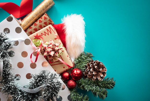 White shopping bag with christmas presents and ornaments on a blue background. copy space