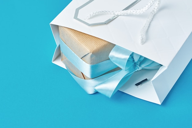 White shopping bag with gift box on blue background, top view