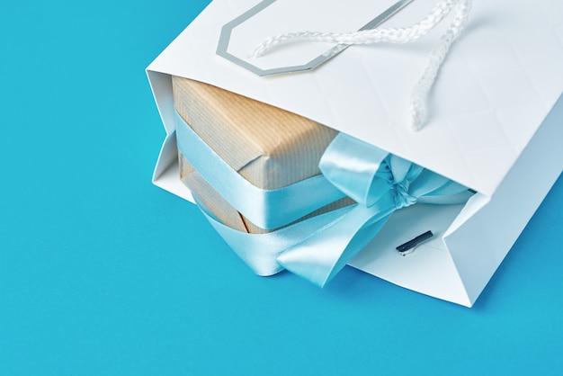 青色の背景、上面にギフトボックスと白いショッピングバッグ
