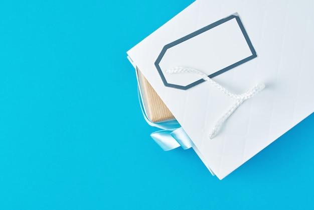 青い表面、上面にギフトボックスと白いショッピングバッグ