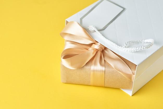 黄色の背景、トップビューでギフトボックスと白いショッピングバッグ