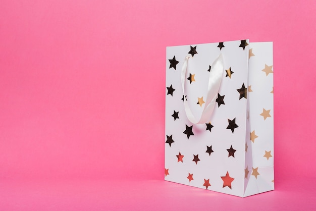 White shopping bag with star shape pattern on pink background