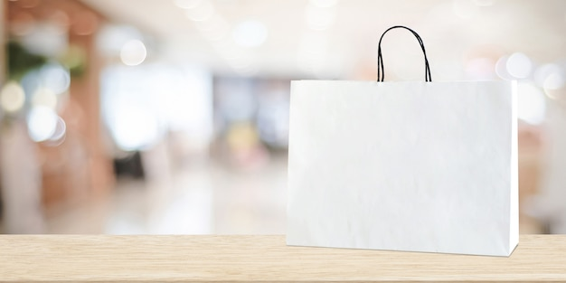 White shopping bag on wooden table over blurred store background, business, template, product display montage background