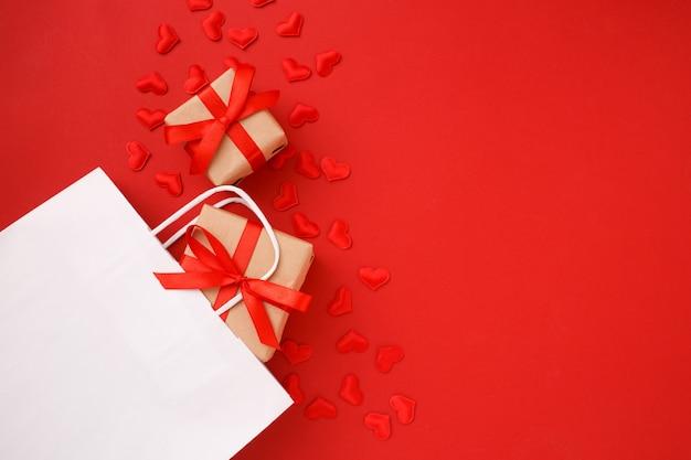赤いハートの紙吹雪と赤のギフトと白いショッピング紙袋。バレンタインデー 。平面図、平置き