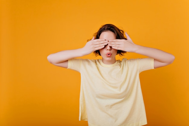 White short-haired girl wears ring plays in hide and seek. indoor photo of brunette lady in oversize t-shirt covering eyes.