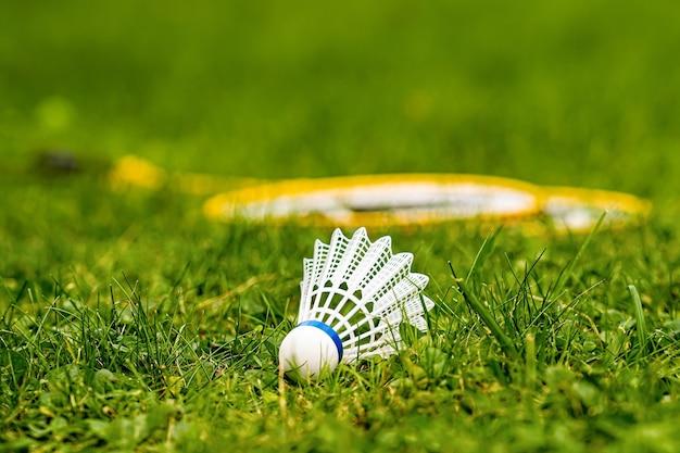 ぼやけた背景に黄色のバドミントンラケットと緑の牧草地の白いシャトルコックのクローズアップ