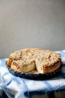 白いシチリアのフォカッチャ。青と白のテーブルクロスで提供されるセラミック皿に玉ねぎ、ハーブ、チーズを添えた伝統的な焼きたてのパンのスライスケーキ。