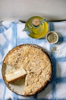 白いシチリアのフォカッチャ。青と白のテーブルクロスにオリーブオイルを添えたセラミック皿にタマネギ、ハーブ、チーズを入れた伝統的な焼きたてのパンスライスケーキ。フラットレイ、スペース