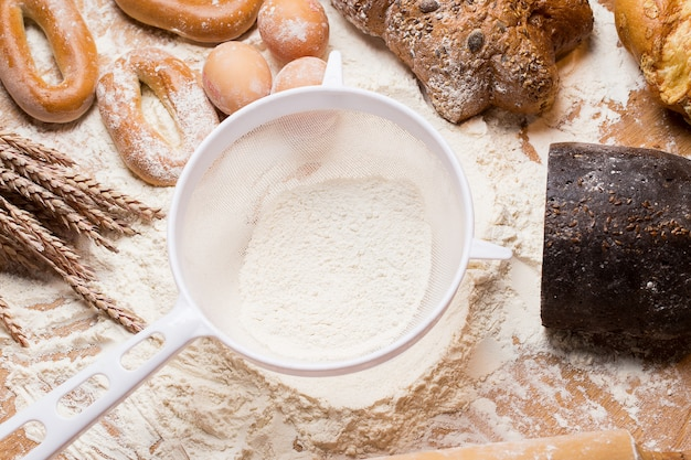 White sieve with flour and bread