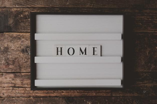 木製の茶色の壁に「家」と書かれた白い看板