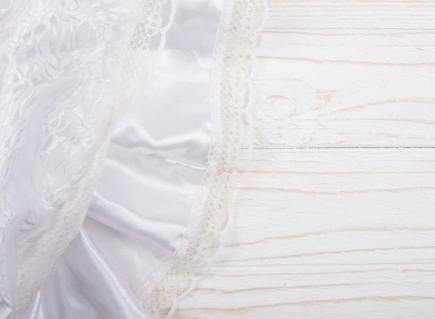 White silk and lace against a white wooden background