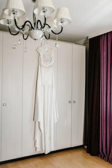 Белое шелковое свадебное платье на вешалке на деревянном фоне комнаты. красивое платье невесты перед церемонией.