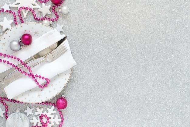 Белая, серебряная и розовая рождественская сервировка стола с елочными украшениями