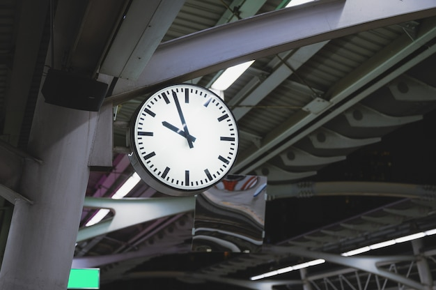 White simple clock hanging on pole in station