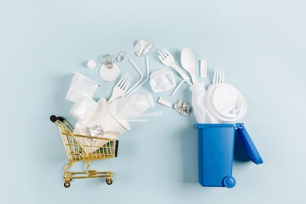 Белый одноразовый пластик, падающий из корзины для мусора. концепция окружающей среды, загрязнения. плоская планировка, вид сверху