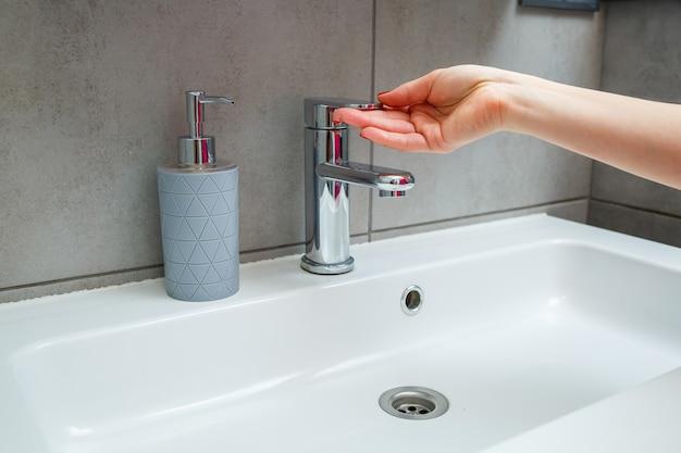 バスルームに銀の蛇口が付いた白いシンク。手用の液体石鹸が入った灰色の缶。水道水をオンにする、個人の手指衛生