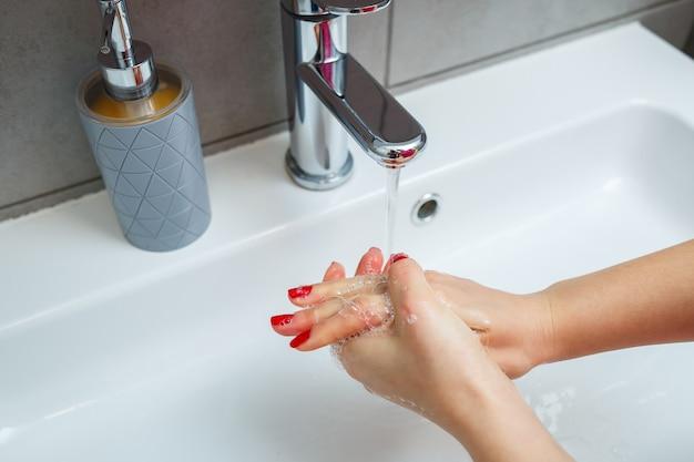 バスルームに銀の蛇口が付いた白いシンク。手用の液体石鹸が入った灰色の缶。水道水をオンにして、個人の手指衛生。流水での手洗い