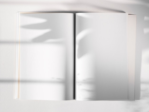 White sketch book on a white background with a leaf shadow