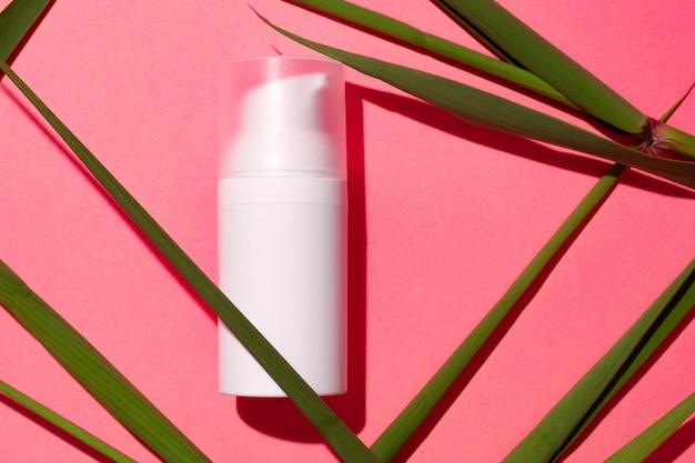 ピンクの背景広告コンセプトの白いスキンケア製品チューブ