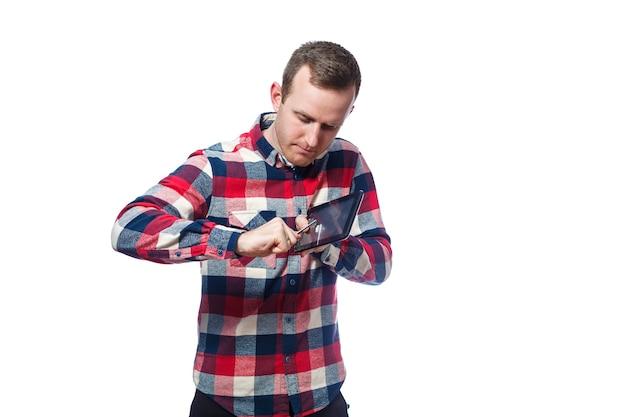 白い肌の男性フリーランサー、修理工がタブレット画面の保護フィルムを引っかいて剥がします。シャツを着ています。感情的な肖像画。白い背景で隔離