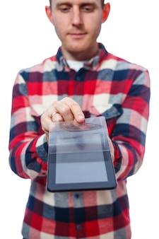 Белокожий фрилансер-ремонтник царапает защитную пленку на экране планшета и снимает ее. в рубашке. эмоциональный портрет. изолированные на белом фоне