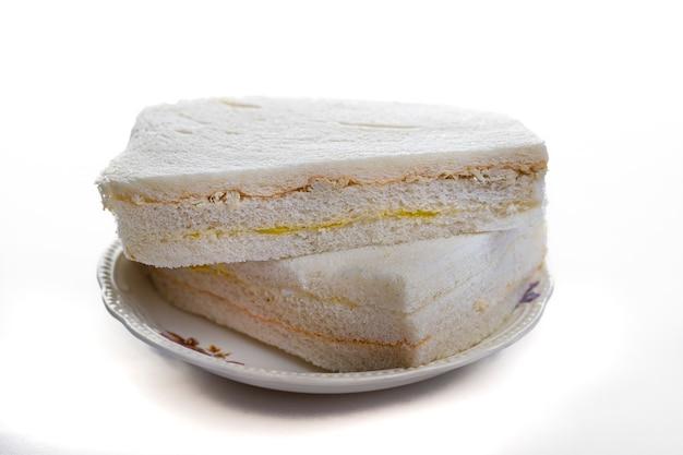 접시와 같은 색상의 배경에 흰색 슬라이스 빵 샌드위치.