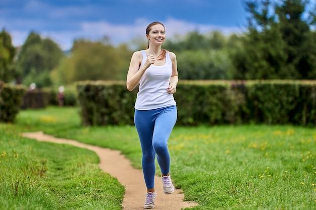 Белая стройная женщина бежит в общественном парке в спортивной одежде