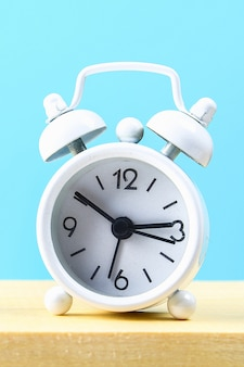 White small alarm clock on a wooden shelf on a blue pastel background
