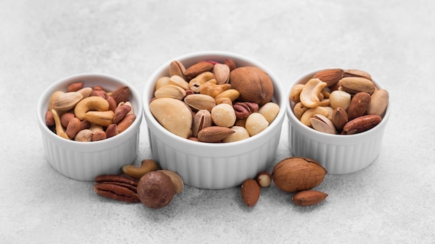 White small bowls filled with assortment of nuts