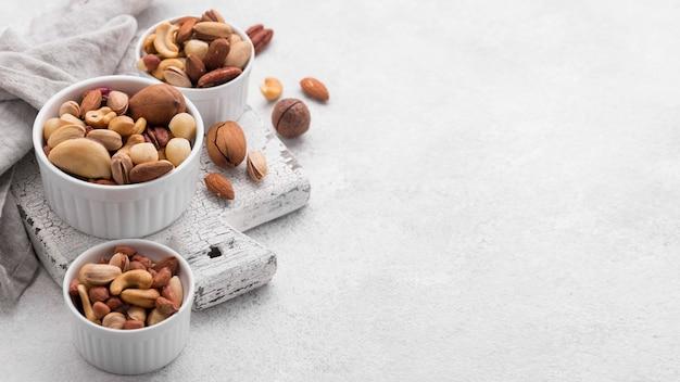 Белые миски, наполненные ассортиментом орехов, копировать пространство