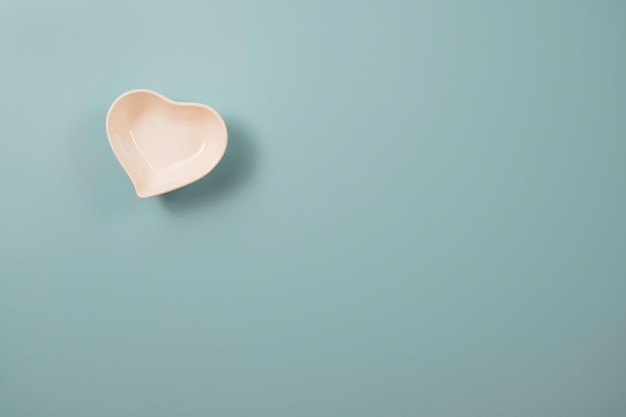 White small ceramic heart shape bowl on blue and copy space on blue background for valentinesã¢â€â™s day concept.