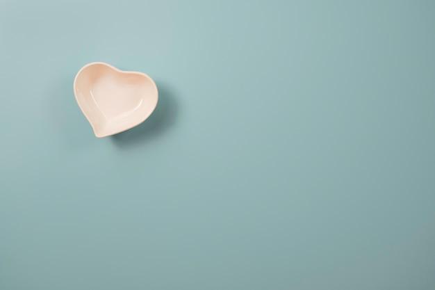 Белая маленькая керамическая чаша в форме сердца на синем и копировальное пространство на синем фоне для концепции дня святого валентина.