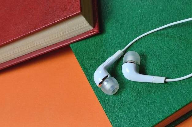 흰색 작은 이어폰 및 도서 오디오 북 개념의 스택.