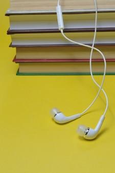 흰색 작은 헤드폰과 책 오디오북 개념의 스택.