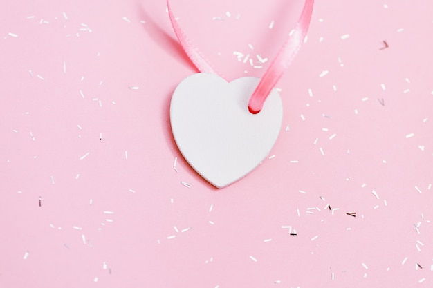White small heart on pink surface with sequins