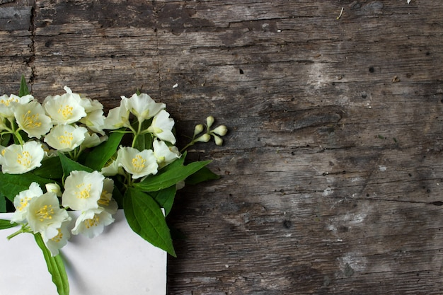 テキストのための灰色の背景スペースに白い小さなバラ花のグリーティングカードのモックアップ