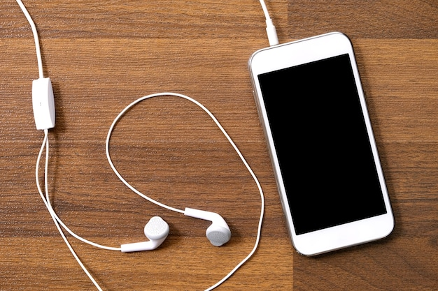 White smart and earphones on wood background