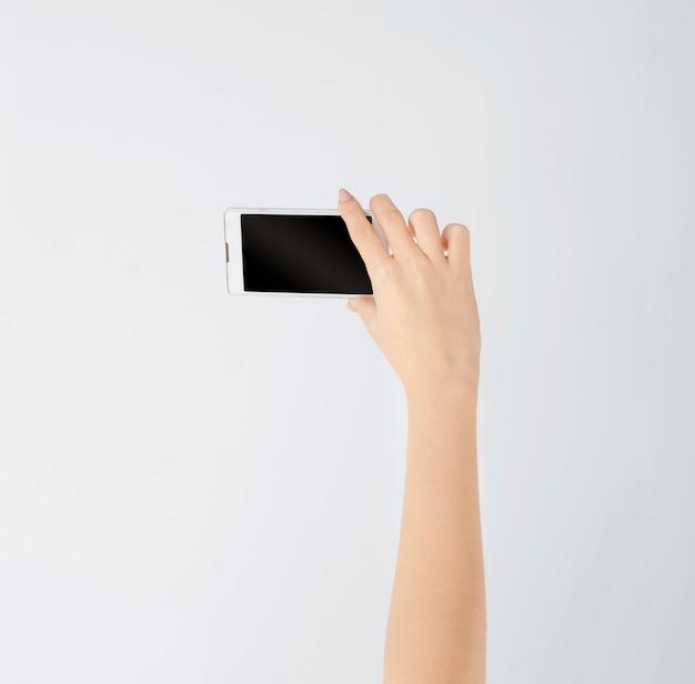 여자의 손에 흰색 스마트 폰