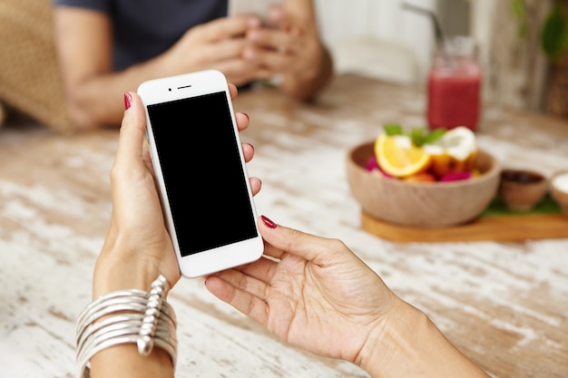 White smart phone with blank copy space screen in woman's hands over cafe table.