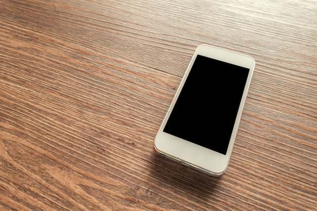 White smart phone with blank screen on wooden desk