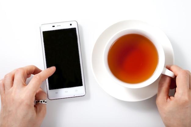 白いスマートフォンと白いガラスのテーブルにお茶のカップとカップを保持し、タッチスクリーンに触れる女性の手