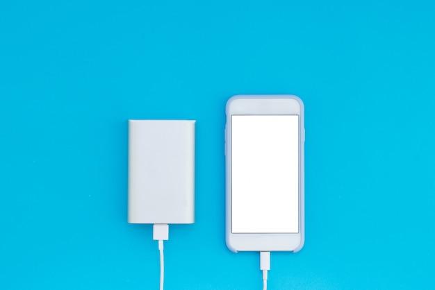 青色の背景に白いスマートフォンと充電器電源銀行。テキストの場所の平面図。