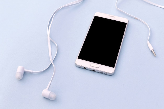 White smartphone and white headphones on blue background.