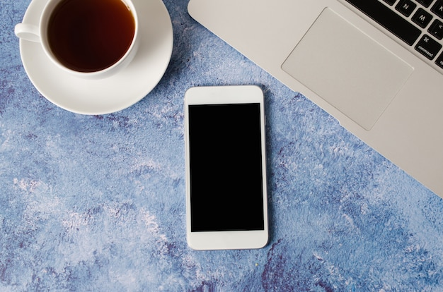 White smartphone with black blank screen on office desk with laptop and cup of tea. mock up of phone.
