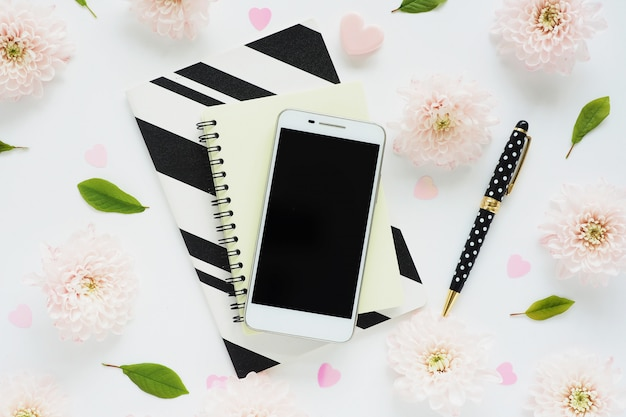 White smartphone with a black screen on yellow and black and white striped notebooks, a black pen with polka dots and many pink flowers of chrysanthemums and green leaves on a white table.